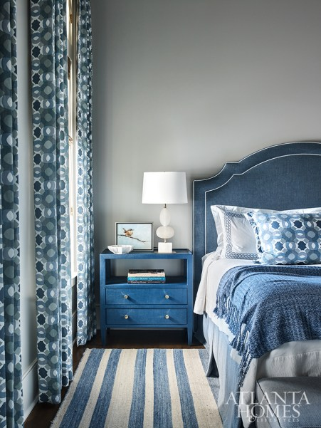 When designing this guest bedroom, Wilkins used blue-and-white-drapery fabric from Raoul Textiles as her starting point, tying in its color scheme with a rug from Keivan Woven Arts, bedding from Home Treasures with a custom upholstered headboard.