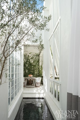 A tranquil pool runs along the front elevation's unique screen of louvered windows, enhancing the connection with nature.