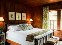 An inn room featuring cozy chestnut paneling and a king bed.