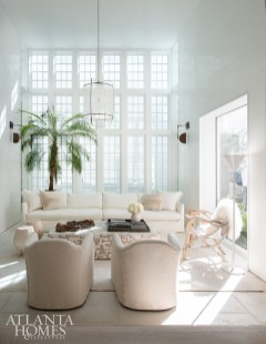 A driftwood chair with a fur throw accents the plush linen-covered sofa and chairs from Verellen in the formal living room. The wall sconces are by Apparatus.