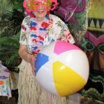 Woman catches beach ball in contest at Island Beach Party.