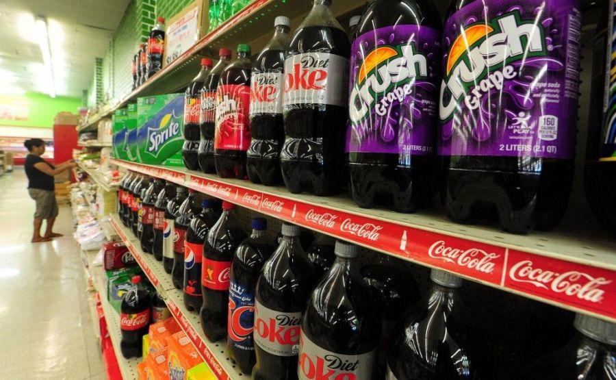 Une femme achète des produits alimentaires près d'un étalage de bouteilles de soda dans un supermarché de Rosemead, en Californie, le 18 juin 2014.