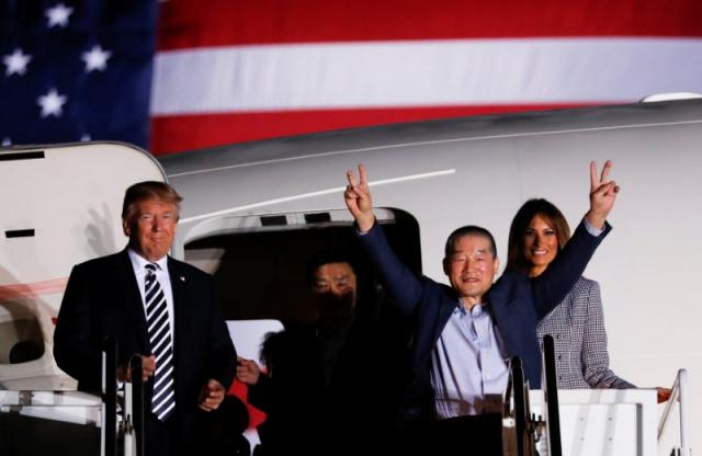 One of the Americans formerly held hostage in North Korea gestures next to U.S.President Donald Trump and first lady Melania Trump, upon their arrival at Joint Base Andrews