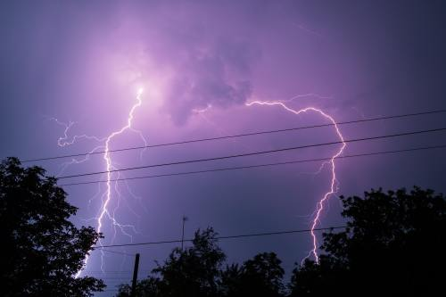 Thunderbolt over the house and dark stormy sky on the background