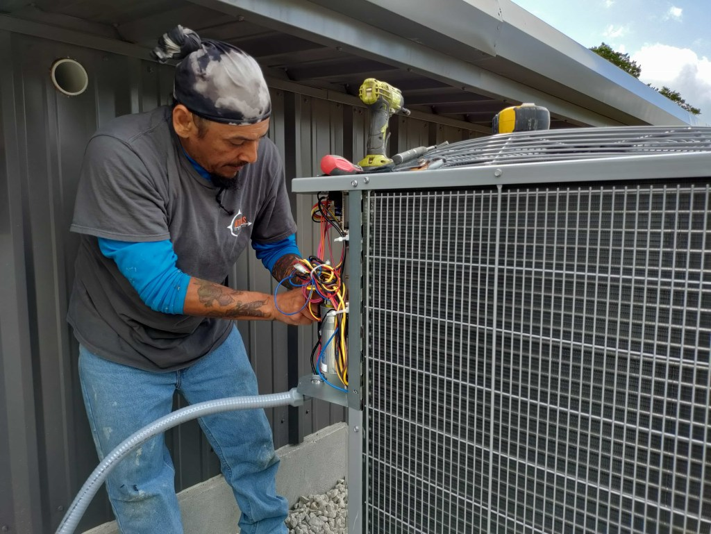 Atlas AC techs working on new ac unit being installed outside
