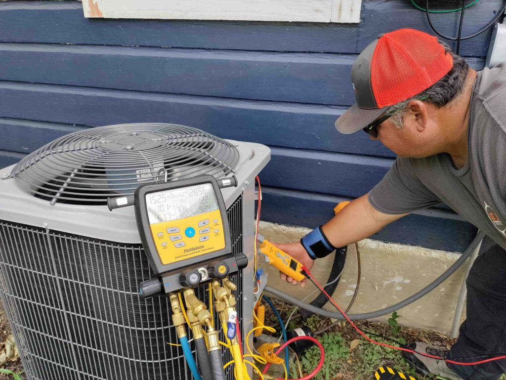 AC technician using digital diagnostic tool during inspection of outdoor air conditioning unit