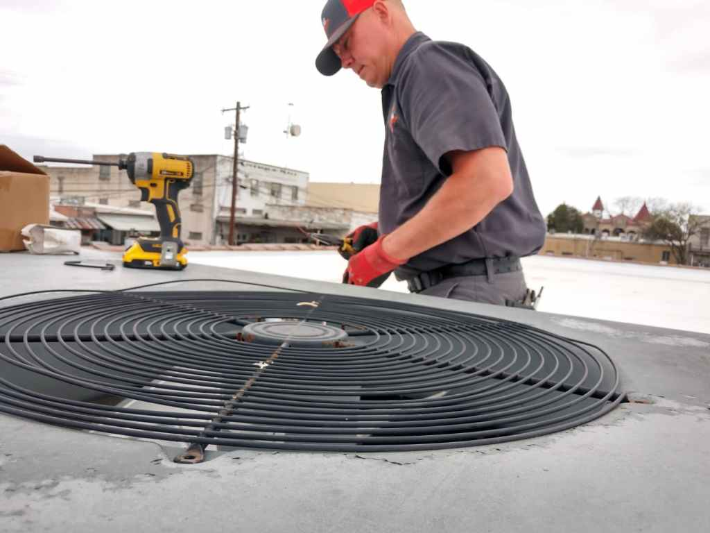 HVAC technician working on air conditioning unit also known as an ac condenser on business rooftop