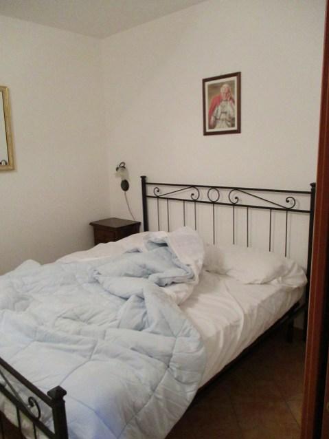 Mein Bett unter dem Bild von Papst Benedikt
