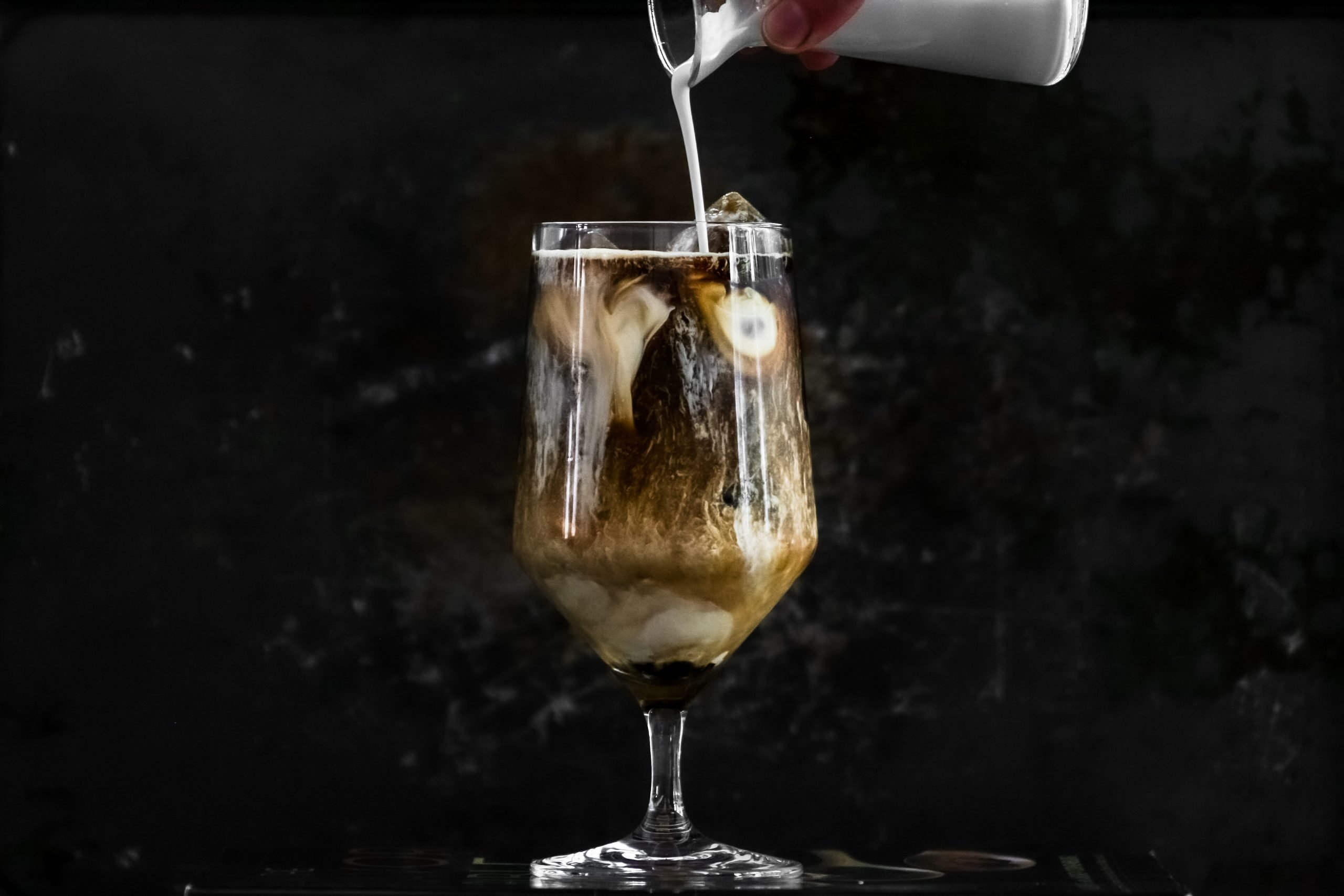 Food photography of pouring cream into iced coffee