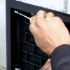 Photo installing and tightening the ATMOX Grilled Solid Vent Plate into the crawl space vent opening