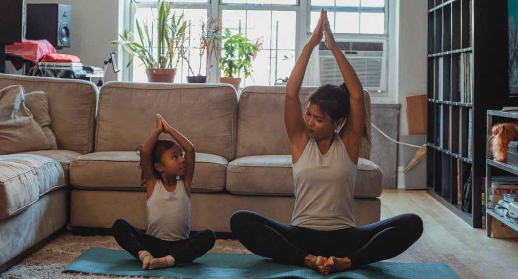 woman doing yoga with a little girl