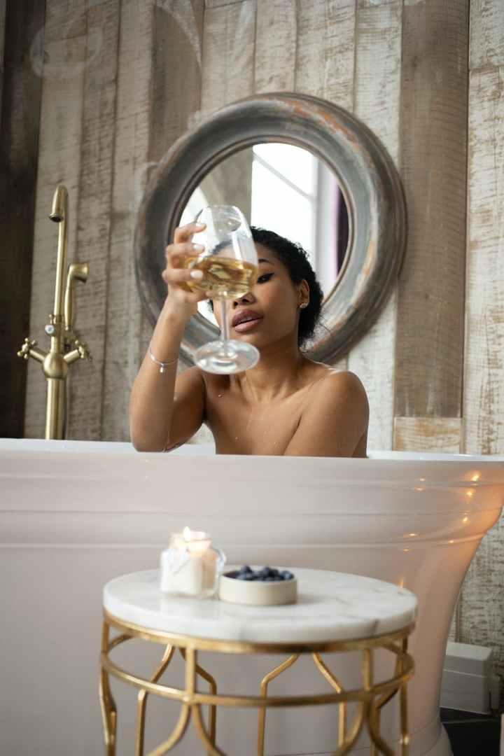 sensual woman in bathtub with wine