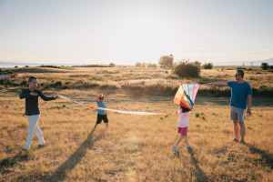 happy family having fun playing with kite on the grass field