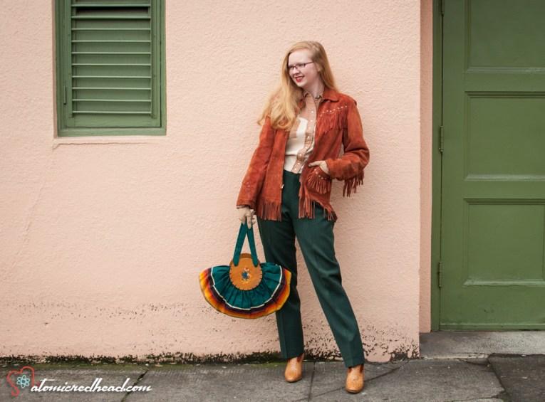 Vintage fringe leather jacket, a vintage western wear top, vintage western wear pants, and cowboy boots.