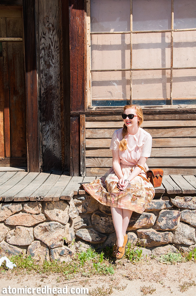 Sitting on the boards and faux rock wall in my outfit I themed for the day, a vintage pale pink nylon blouse, with a vintage border print skirt featuring an illustration of a western town.