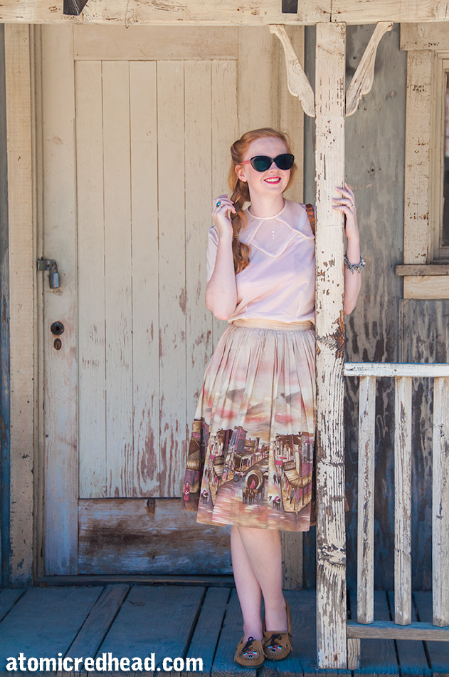 Standing in my outfit I themed for the day, a vintage pale pink nylon blouse, with a vintage border print skirt featuring an illustration of a western town.