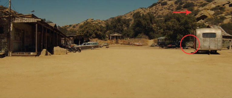 Screencap from Once Upon a Time In...Hollywood. Corriganville playing Spahn Ranch. A line of western style buildings flanks the left. A small house is in the center distance. On the right trees and a trailer work to mostly obscure the low rock walls that were part of the old Corriganville stable. A red circle highlights them. A red arrow points to the rock formation also in the background.