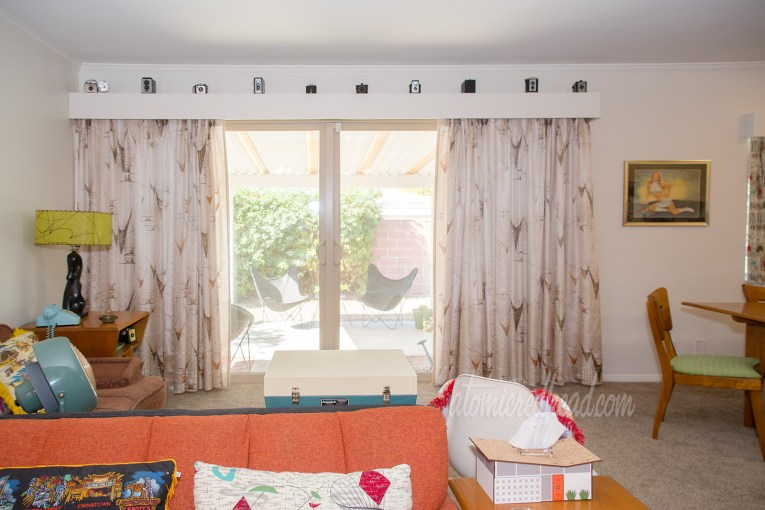 A view into our living room. Along the back wall a long stretch of curtains, open with a view of the backyard, in tan feature brown asymmetrical shapes. The valance above features multiple vintage cameras.