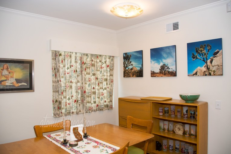 View of our dining room, a maple dining room table, and secretary with built in bookshelf rest against the back wall. The curtains feature mid-century modern versions of flowers.