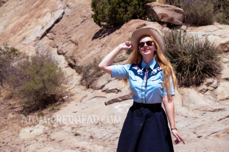 Exploring Vasquez Rocks in a denim skirt, two-tone western shirt, UFO bolo tie by Kesha, and a cream western wear hat.