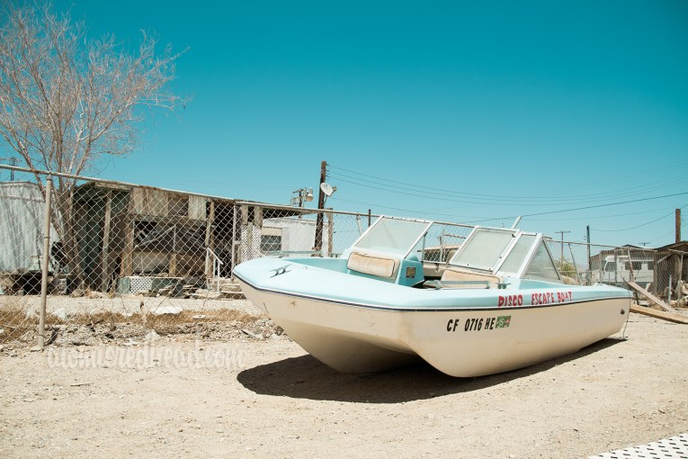 "A boat of white and blue sits fading in the sun, reading ""Disco Escape Boat"""