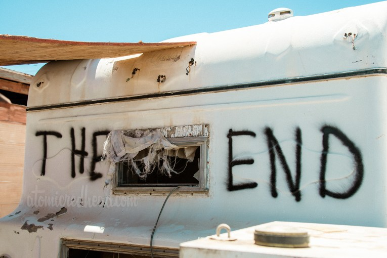 """Vintage travel trailer, spray painted with """"The End"""" on the back"""