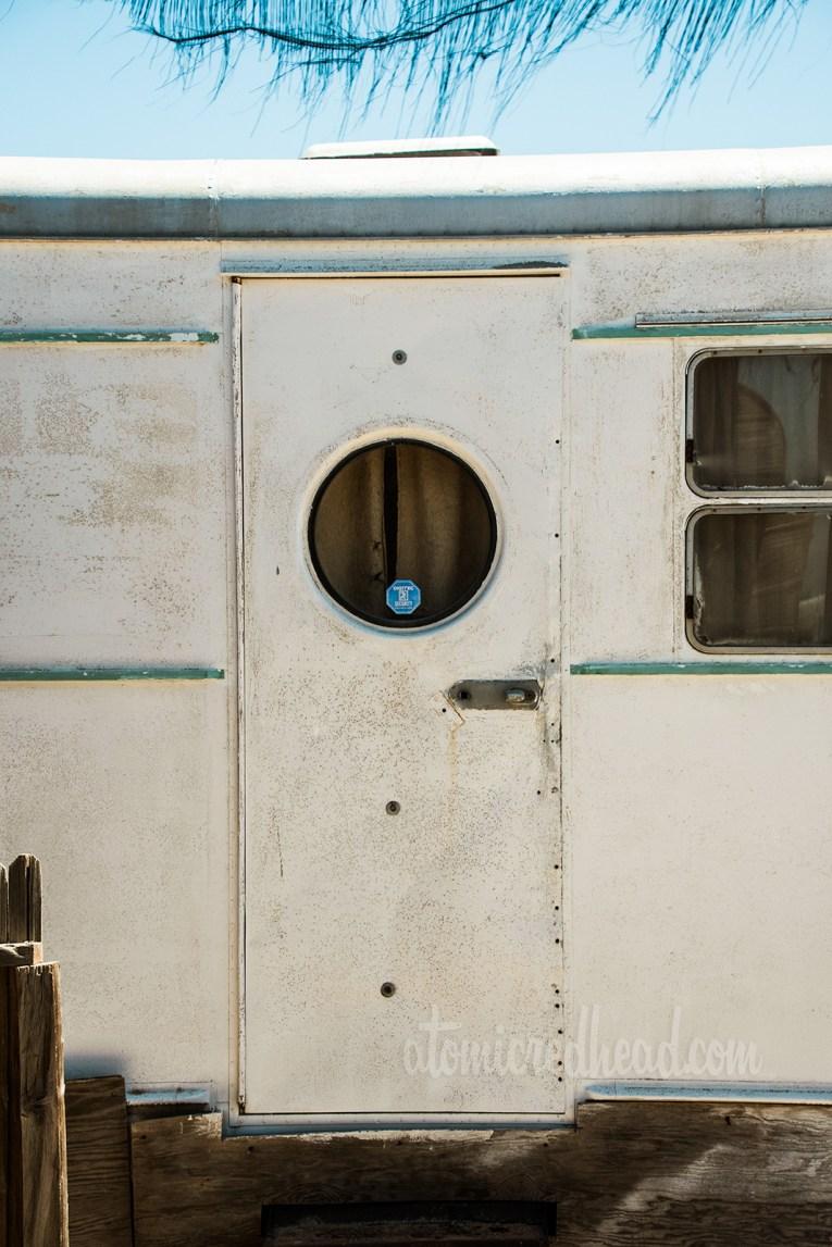 Vintage trailer door, featuring a unique round window.