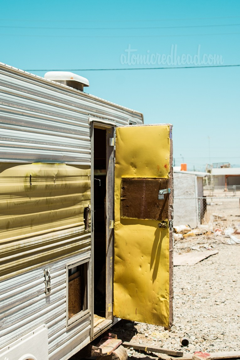 Two tone yellow and white trailer, with the door open. Beat up and faded.