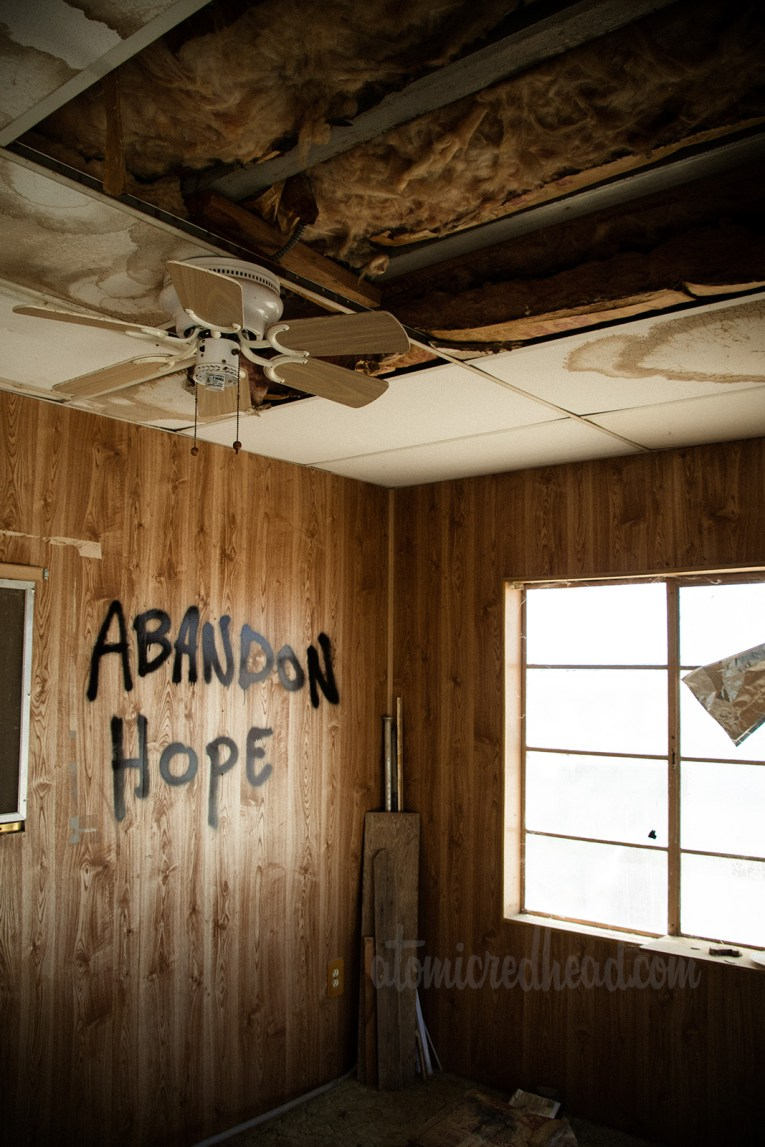 """Inside a trailer, with a broken drop down ceiling, faux wood paneling, and has been tagged with """"Abandon Hope"""""""