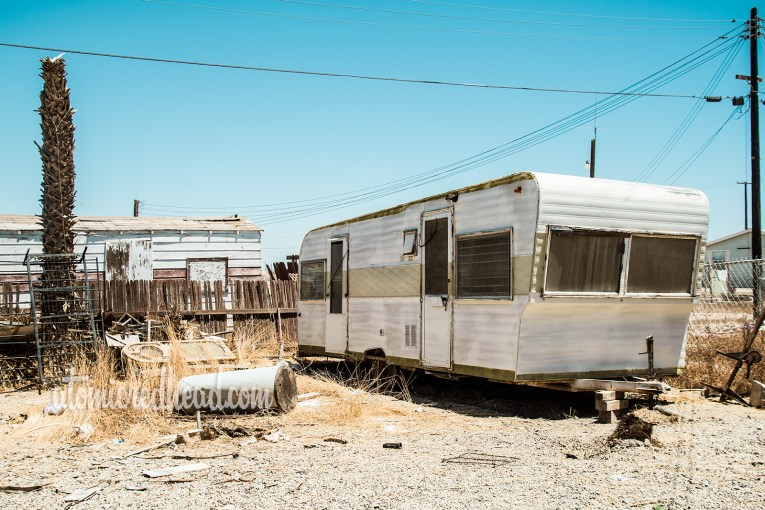 An abandoned trailer, faded, rusty, and surrounded by junk.
