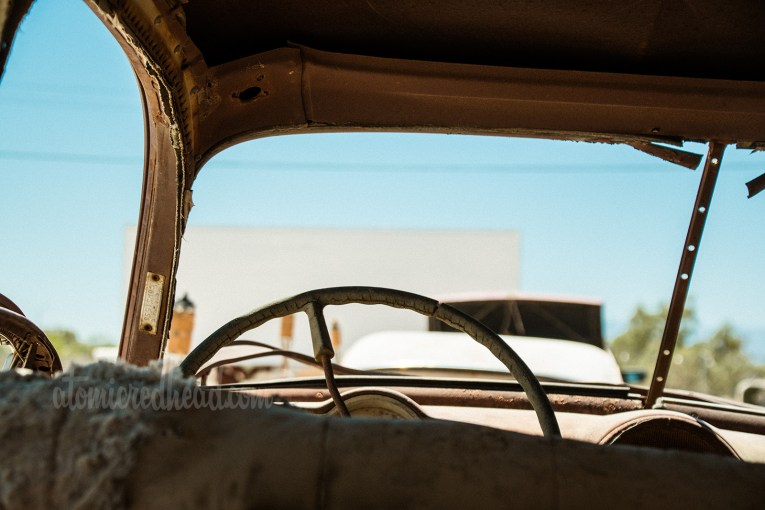 Art Installation - The Bombay Beach Drive-In, a faux drive-in with old, junk cars and a large trailer painted white to emulate a screen. Close up of interior of a car, over the steering wheel out toward the screen.