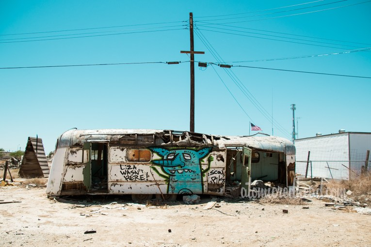 """An abandoned vintage trailer that has suffered a fire, and been tagged. One tag reads """"Liza Wasn't Here"""""""