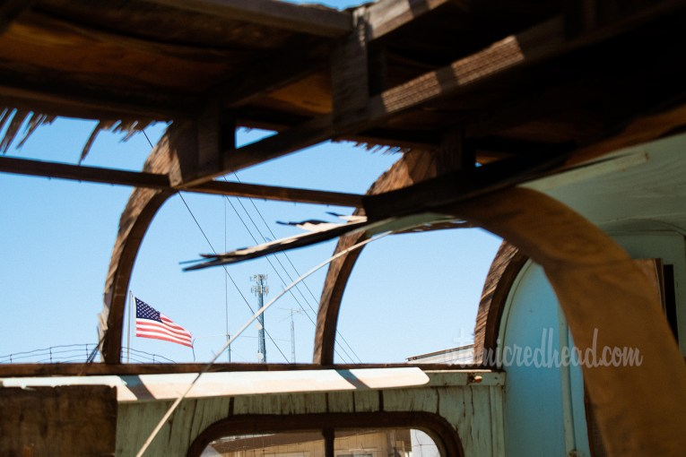 Part of the ceiling is gone of a travel trailer, through it the American flag waves.