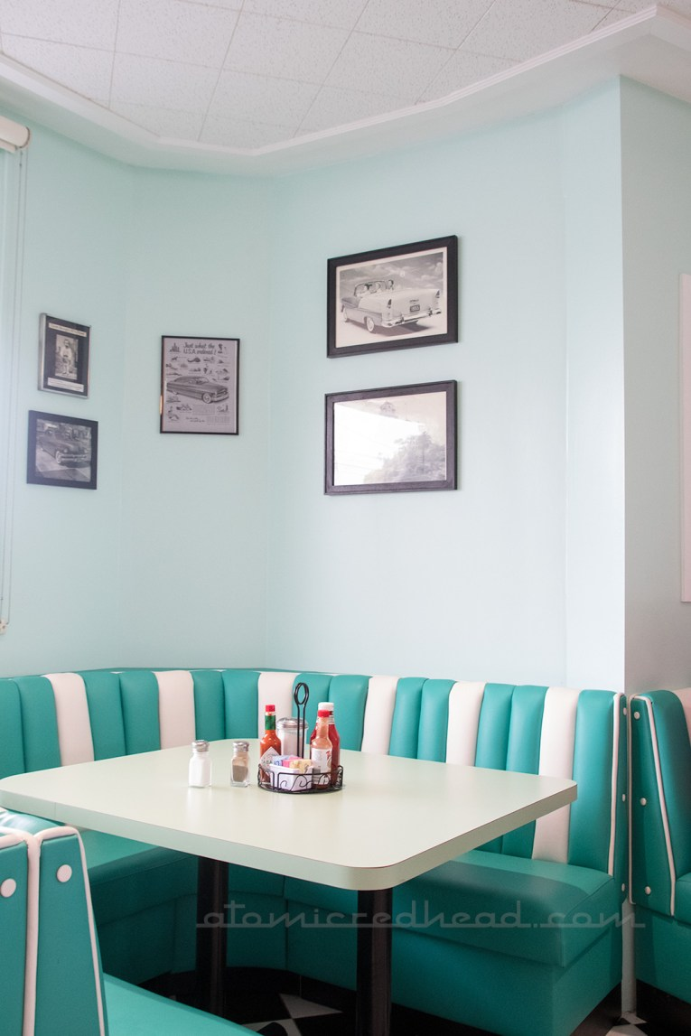 Interior of George's 50s diner, pale blue walls with turquoise and white tufted booths.