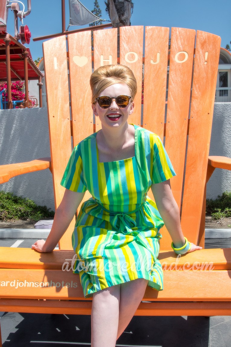 A massive orange lawn chair sits in HoJo's parking lot for photos, me atop it in my Swirl dress.
