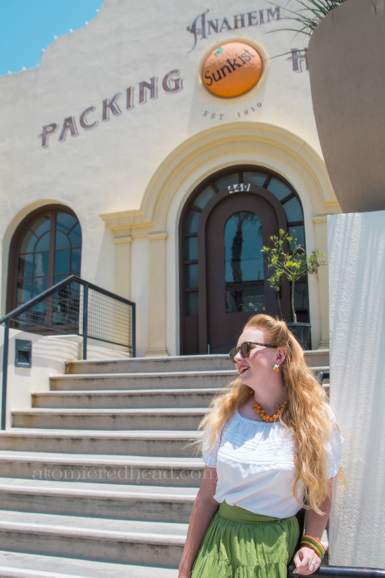 Standing in front of the Packing House, a Mission style building, in a white peasant top, green skirt with orange rick-rack, and orange fruit accessories.