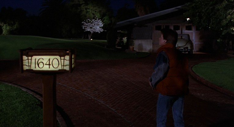 Screencap from Back to the Future - Marty arrives at Doc Brown's House, the garage in the background, the house on the left.