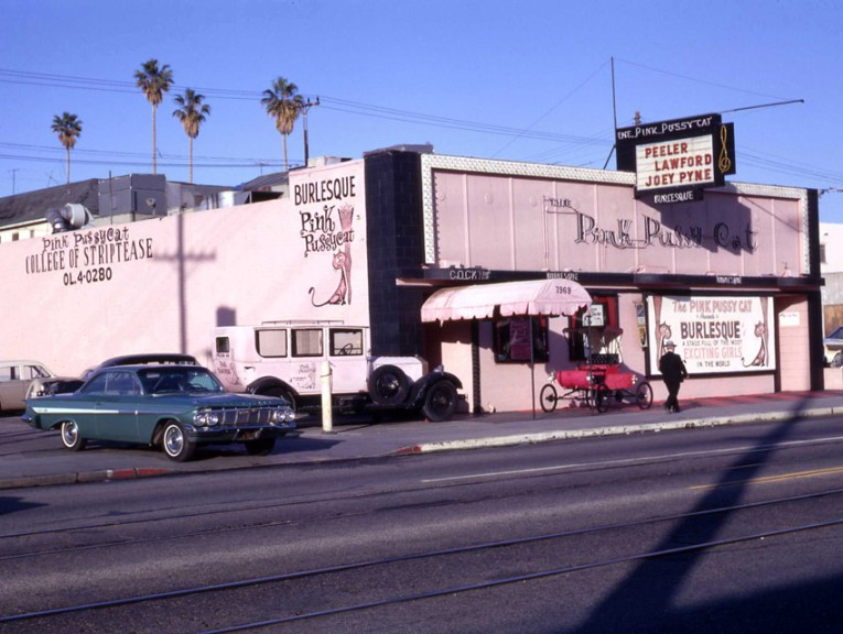 Old photograph of the exterior of The Pink Pussycat, painted pink and black, including a large mural of a cat rubbing against a fishnet covered leg.