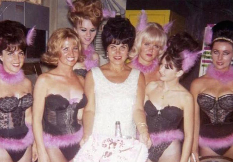 Alice in a white cocktail dress with her pussycats wearing lacy strapless black tops and pink feather tutus with pink feathers in their hair, emulating cat ears.