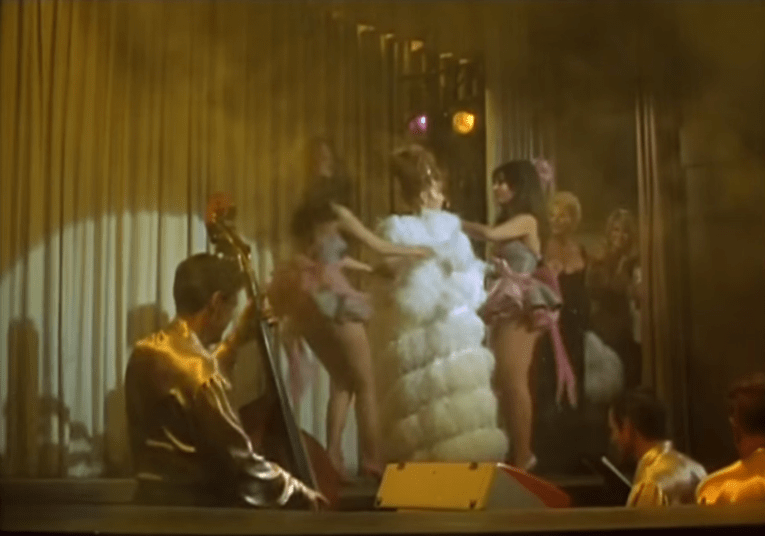 The Pink Pussycat interior as seen in The Swinger, with Ann-Margret being assisted by Pussycats wearing the trademark pink feathers in their hair.
