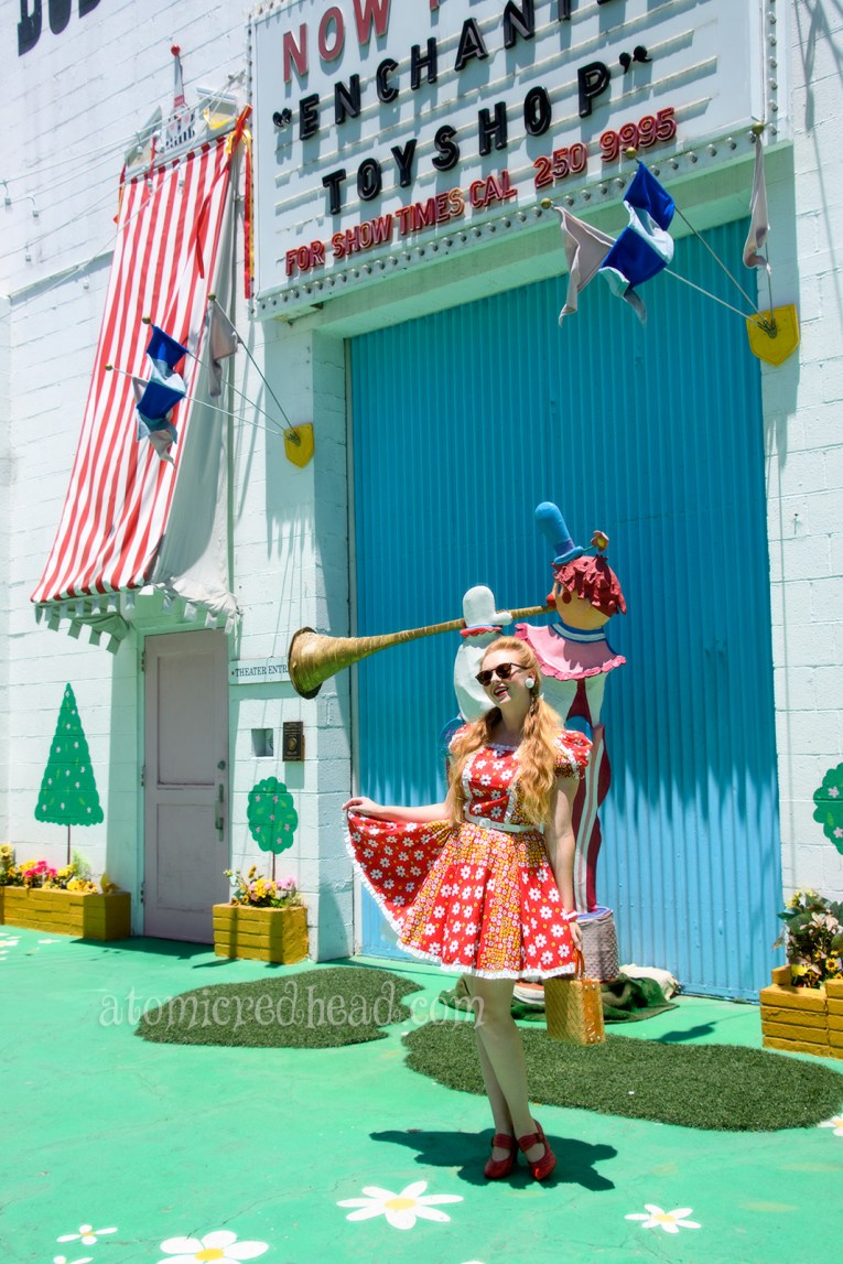 Standing outside of the Bob Baker Marionette Theater. Wearing a red square dancing dress with yellow and white flowers.