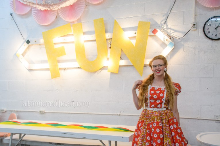 """Standing inside the party room where """"FUN"""" is spelled out in large yellow letters."""