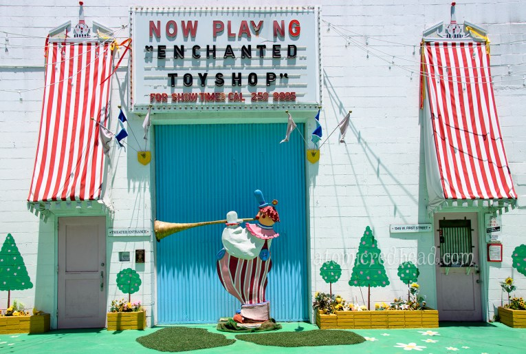 The exterior of the theater, with feature red and white stripe awnings, a large blue wall with a fat clown blowing a trumpet.
