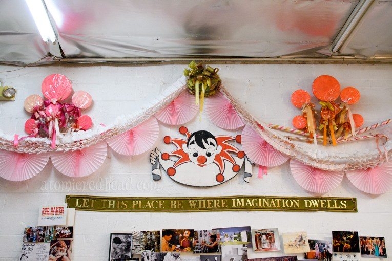 "A banner reading ""Let this place be where imagination dwells"" hangs above photos, a playful hand painted clown looks down."
