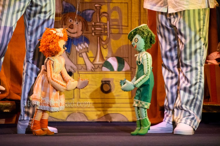 Two rag doll marionettes, a girl in all orange, and a boy in all gree.