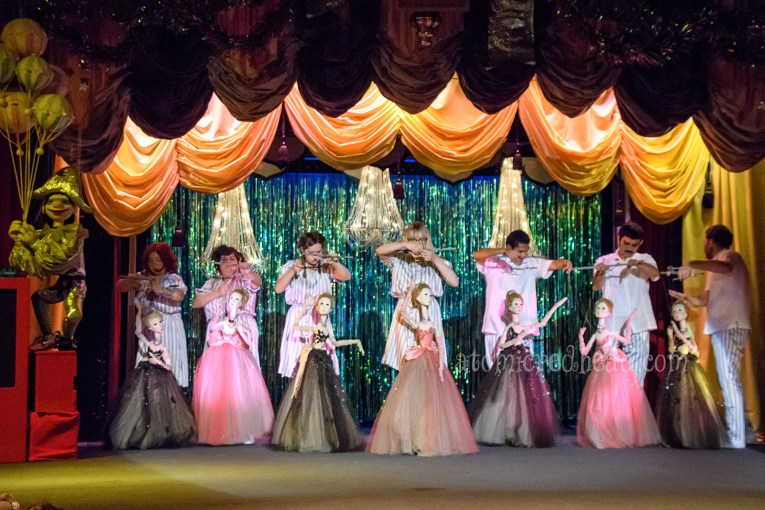Large marionettes of women wearing tulle prom dresses. Some in black, others in pink.