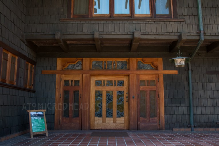 The front door of the Gamble House, teak wood surrounds a stained glass of a tree.