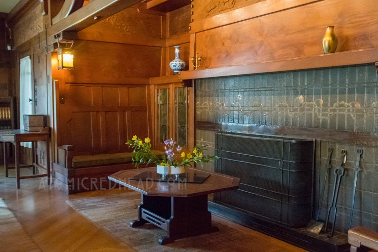 The fireplace of the living room, all rich warm wood, with a dusty green tile fireplace.