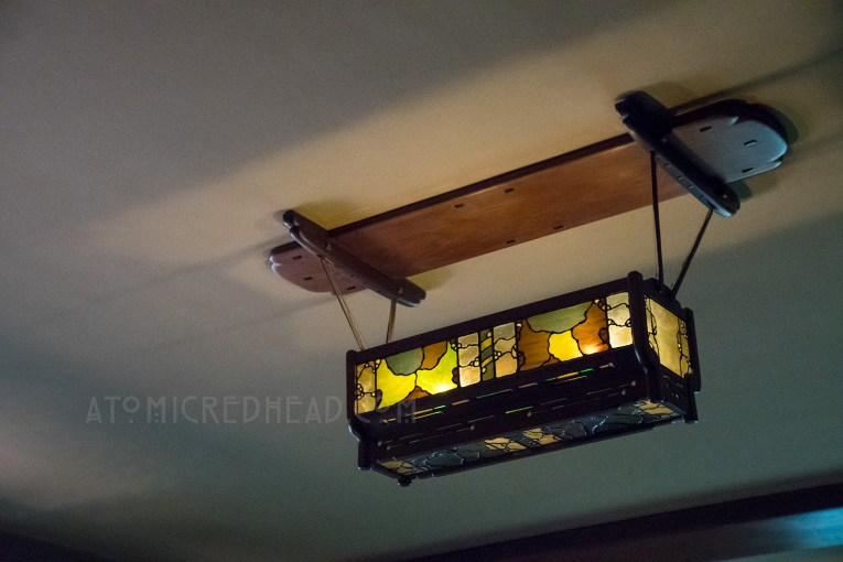 An indirect light fixture of stained glass hangs from the ceiling of the family room.