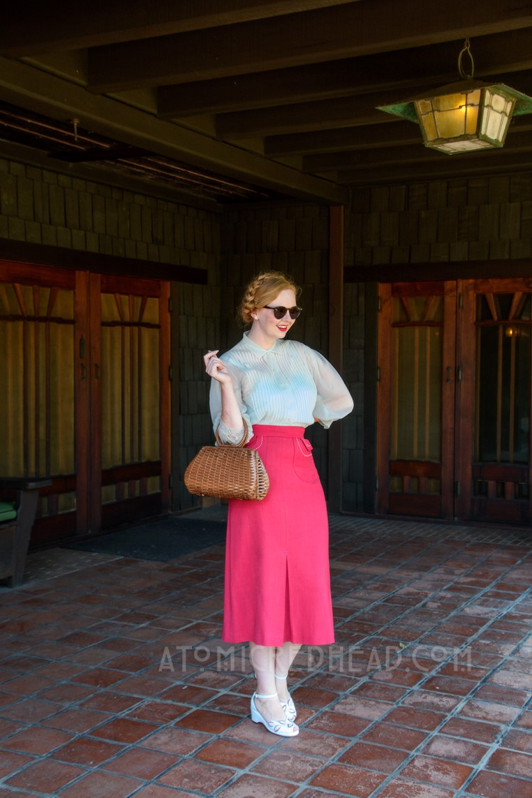 Standing on the back porch of the Gamble House, wearing a pale blue sheer blouse and magenta skirt with white trim, and a brown woven basket purse.